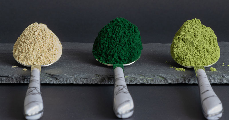 Different greens powders on spoons